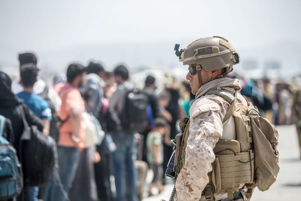A U.S. soldier stands in the foreground in military gear and helmet. In the background, a line of Afghans.