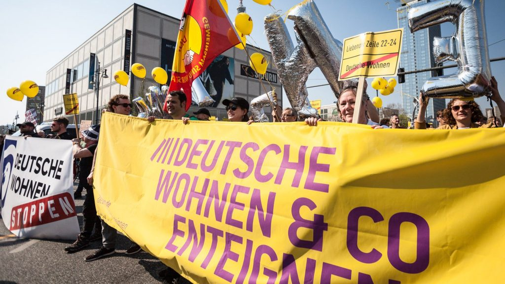 People marching and holding a big yellow and purple banner in favor of expropriating Berlin landlords.