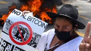 """A woman in El Salvador wears a brimmed hat and a black mouth covering and holds a sign that says """"No Al Bitcoin"""" (No to bitcoin). There is a fire behind her."""