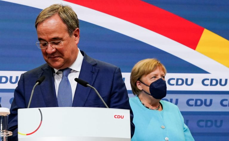 On the left, Armin Lachet, the new leader of the German CDU party. He's a man in his 50s wearing glasses and a suit. In the background, German chancellor Angela Markel wears a mask and light blue suit.