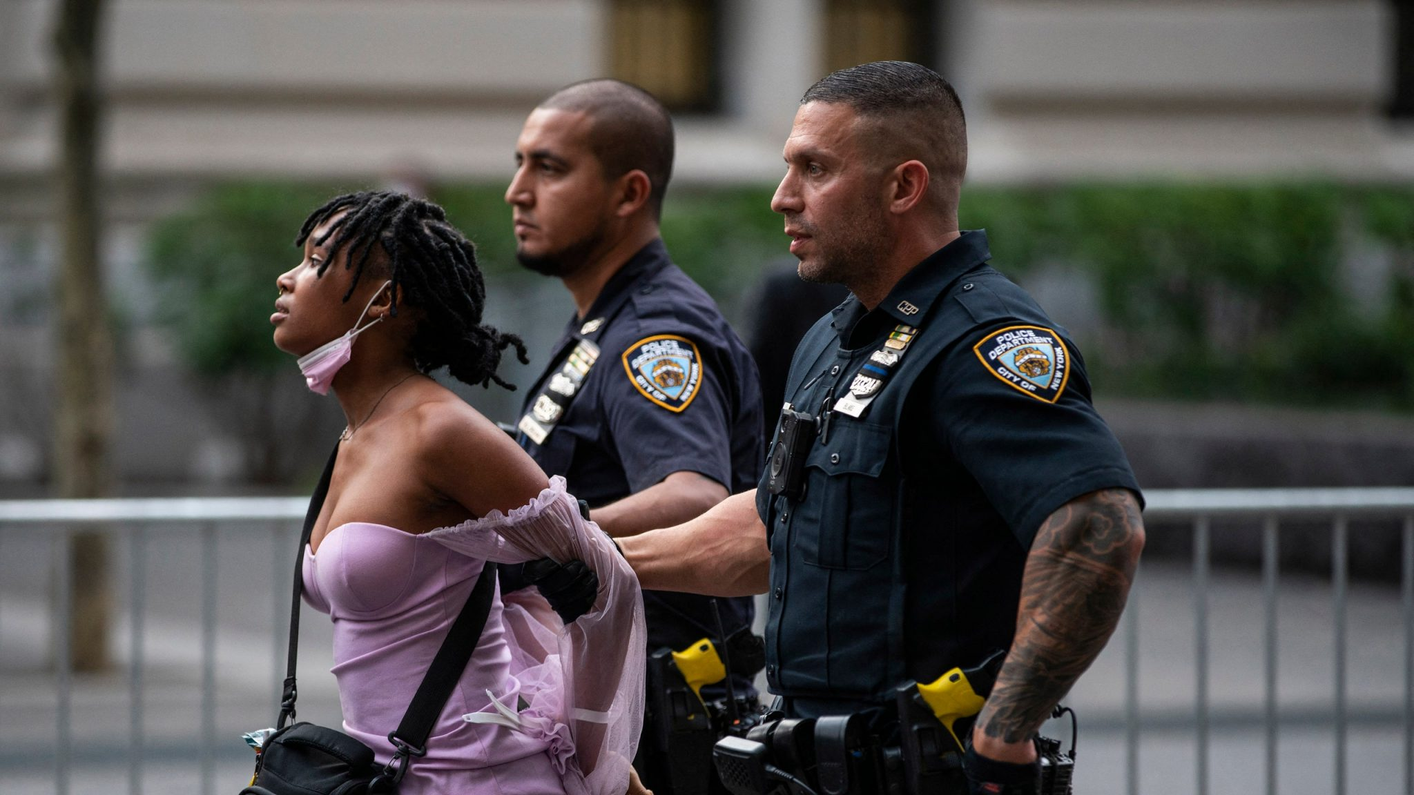 A black person wearing a purple shirt with a black crossbody bag is being restrained by two police officers.