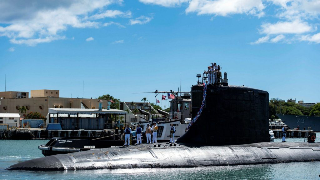 A submarine in a harbor, soldiers in the background.