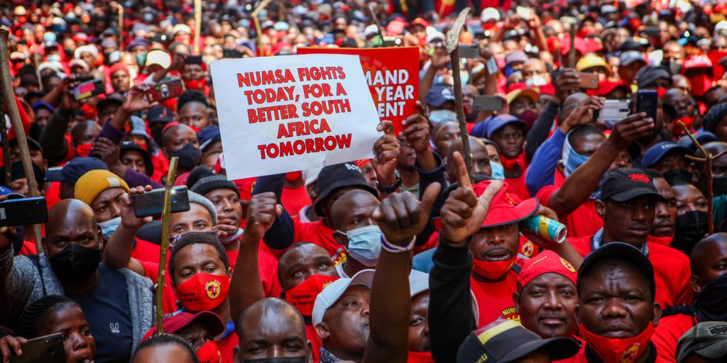 """A sea of South African NUMSA workers wearing red t-shirts. A sign says """"NUMSA fights today for a better South Africa tomorrow."""""""