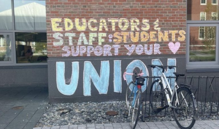 """A brick wall, on which someone has written in colorful chalk, """"Educators & Staff: Students Support Your Union!"""""""