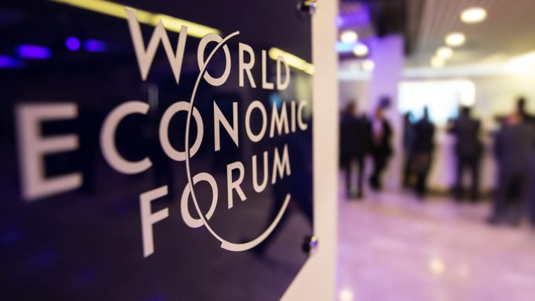 Inside a World Economic Forum building, the logo is on the left.