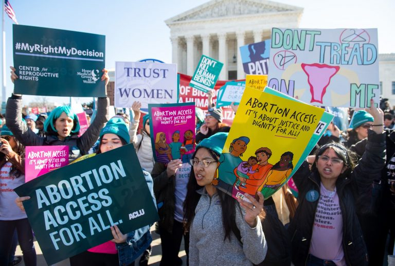 People at a pro-choice protest in front of a government building in Washington, D.C.