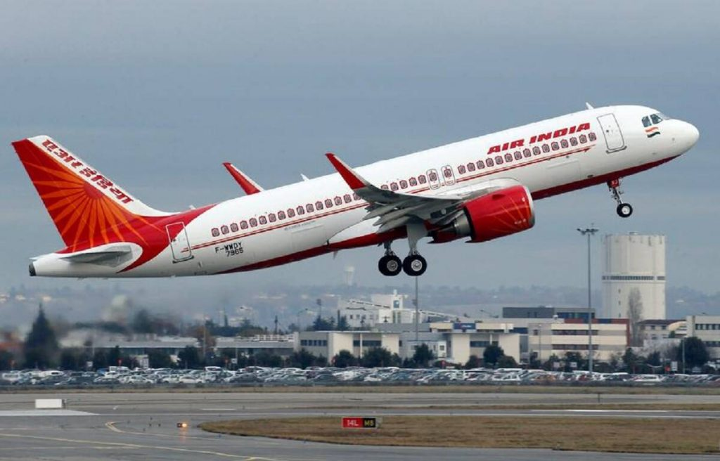 A white and red Air India plane takes off.