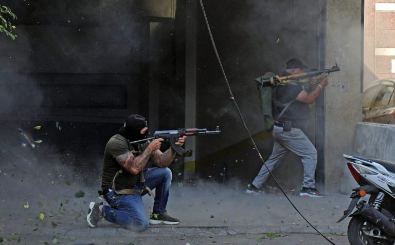 Two men kneel with machine guns and face to the right during clashes in Beirut on October 14.