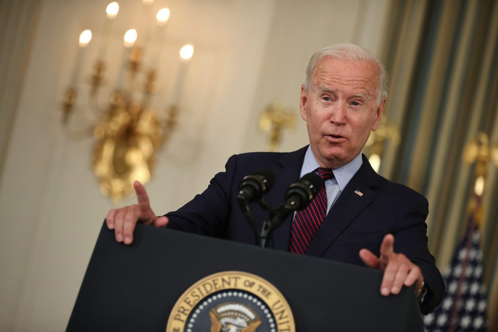 Biden is at the podium with golden chandeliers and lighting fixtures in the background.
