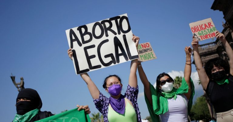 """Chilean women wear grean and hold up signs at an abortion rally. The sign reads """"Aborto legal"""" or """"Legalize abortion"""""""