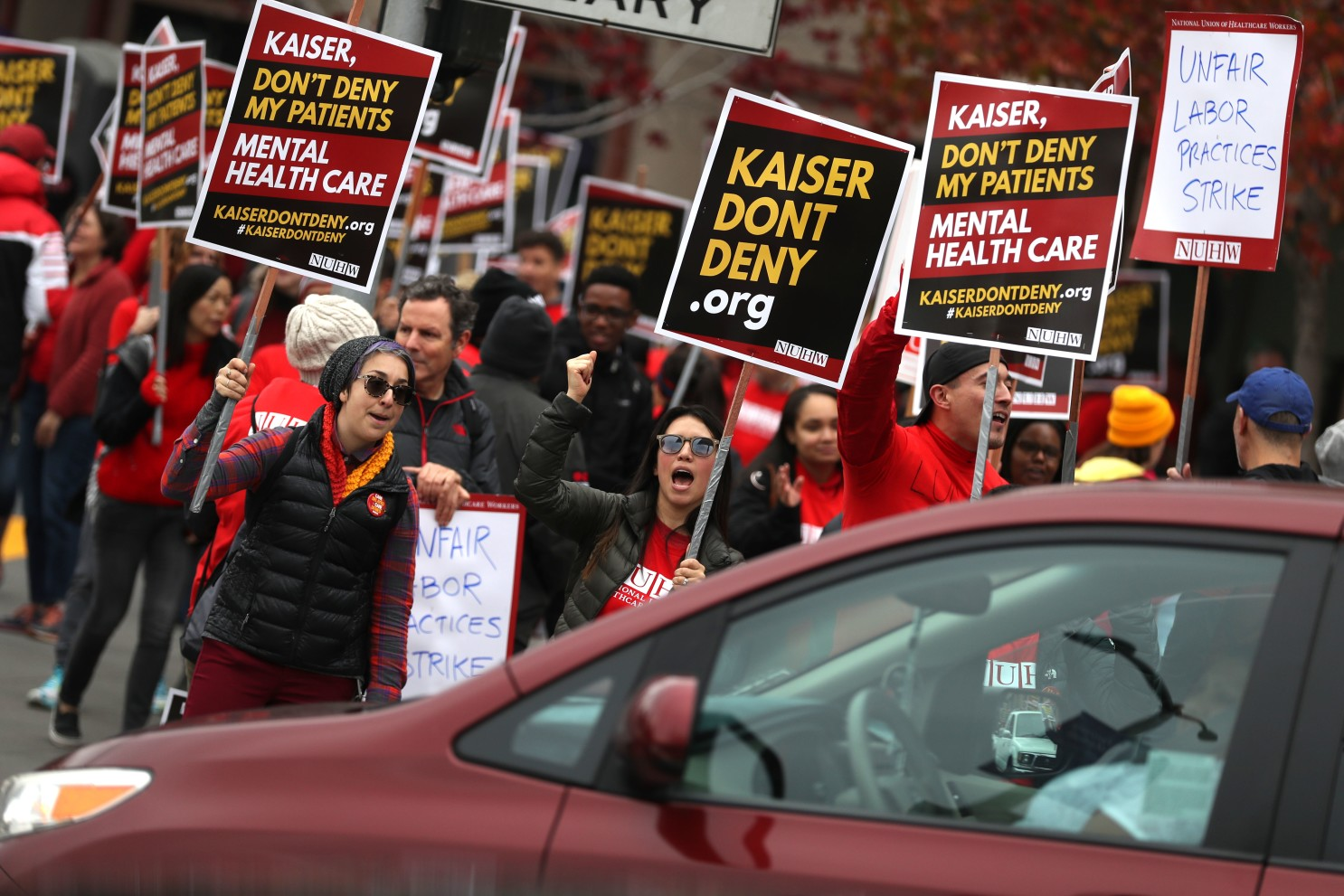 Healthcare workers dressed in red hold up protest signs against Kaiser Permanente while a car drives by.