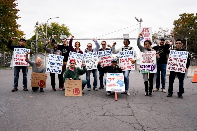 12 people hold signs and hold their fists raised on the Kellogg's picket line.