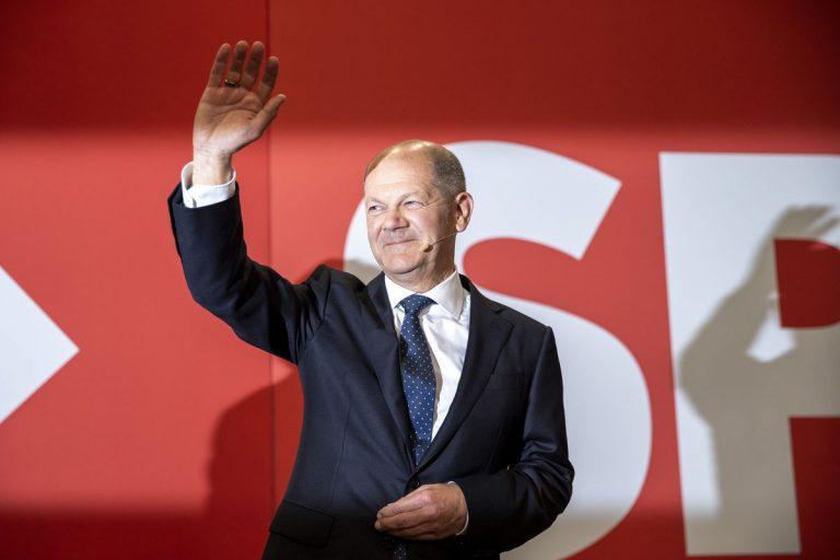 Standing in front of a red background with SPD written in white, Olaf Scholz, a balding man in his 50s, is wearing a suit, smiling, and waving at the audience.