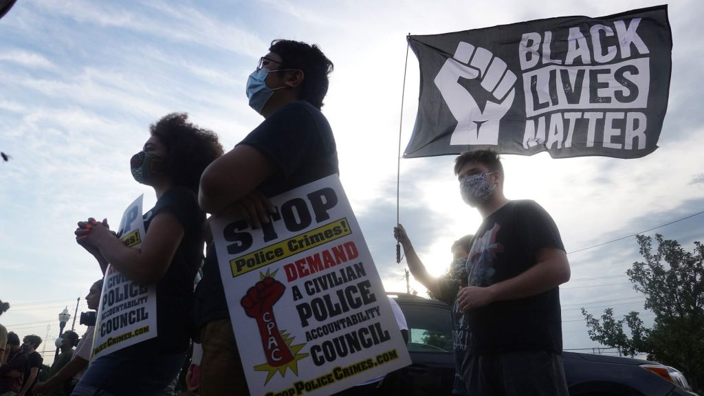 Four protesters of different races, all wearing face masks and black shirts, face to the left while holding Black Lives Matter signs. The sun shines brightly behind them in a partly cloudy sky