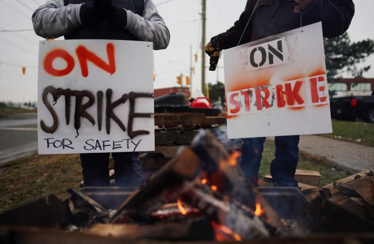 """Two workers hold signs that say """"On strike,"""" in the foreground is a small fire."""