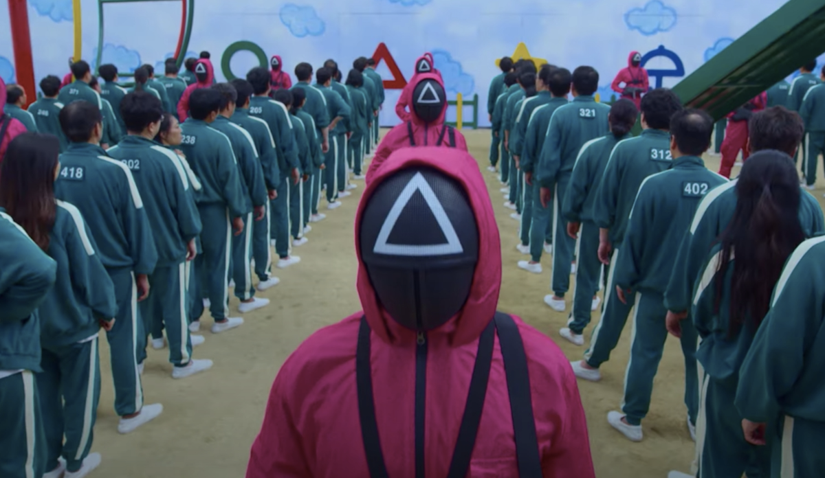 A figure in a pink track suit surrounded by figures in green track suits, a scene from the show Squid Game.