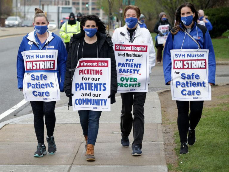 """Four female St. Vincent nurses walking side by side on a sidewalk. They are holding signs that read """"Safe Patient Care"""" and """"Picketing for our patients and our community."""""""