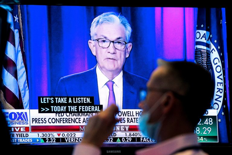 A screen displays a statement by Federal Reserve Chair Jerome Powell as a trader works on the floor of the New York Stock Exchange in New York City, U.S., September 22, 2021.
