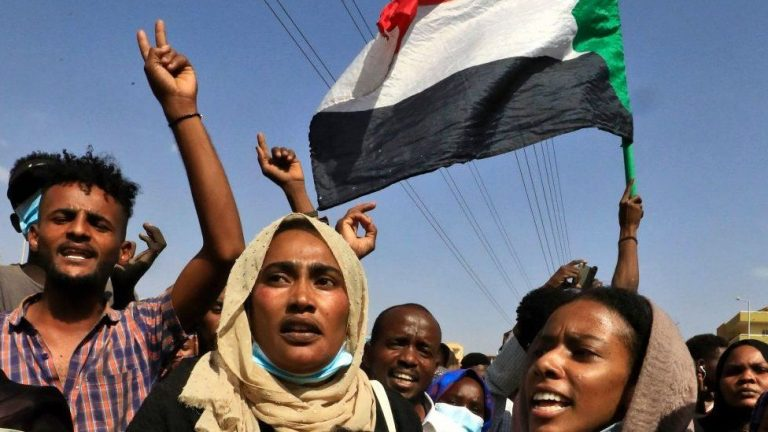 A Sudanese man and two Sudanese women marching against the coup in Sudan in October 2021. A Sudanese flag in the background.